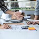 Engenheiros utilizando o planejamento de obras para prever problemas
